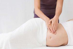 A masseuse giving a woman a pregnancy massage